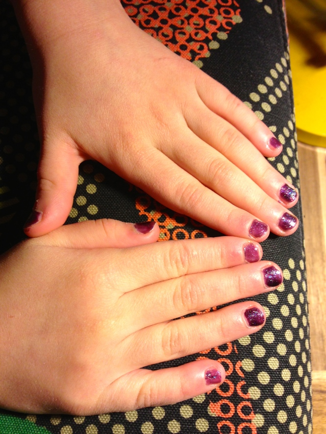 Isabella waiting for her nails to dry. One coat purple sparkle, one coat clear with glitter.